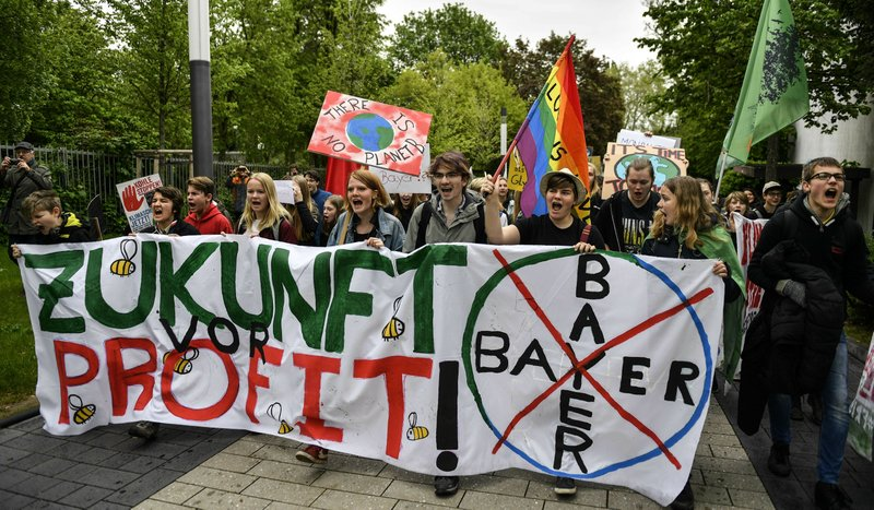 People attend a protest rally outside the annual general meeting of the Bayer stock company in Bonn, Germany, Friday, April 26, 2019. (AP Photo/Martin Meissner)