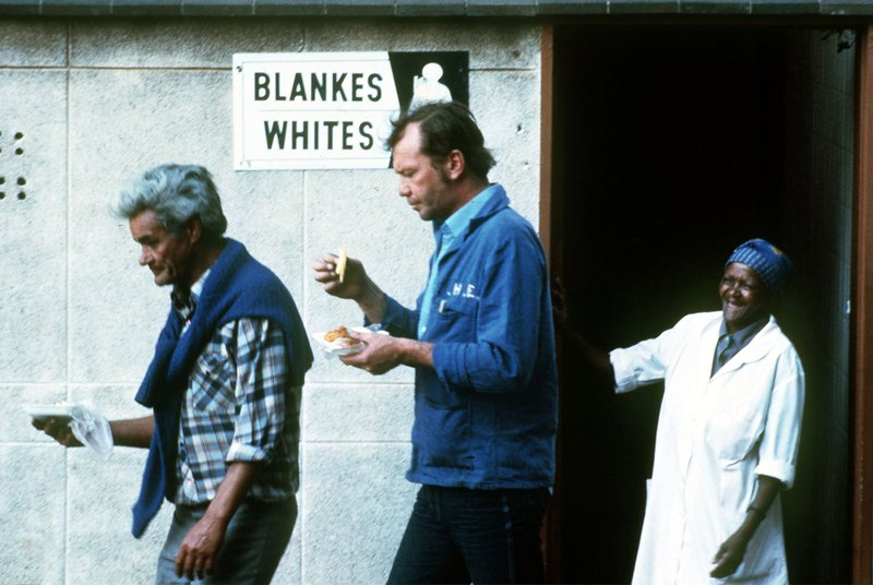 FILE - In this photo taken Jan. 1, 1985 two men exit public toilets reserved for whites only in downtown Johannesburg. (AP Photo/David Van Gur, File)