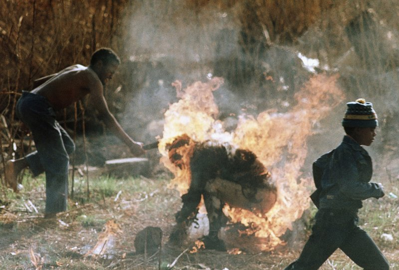 FILE - In this Sept. 15, 1990 file photo a youth clubs the burning body of a Zulu man beaten and burned to death as a suspected Inkatha faction member in Soweto, South Africa, Sept. (AP Photo/Greg Marinovich, File)