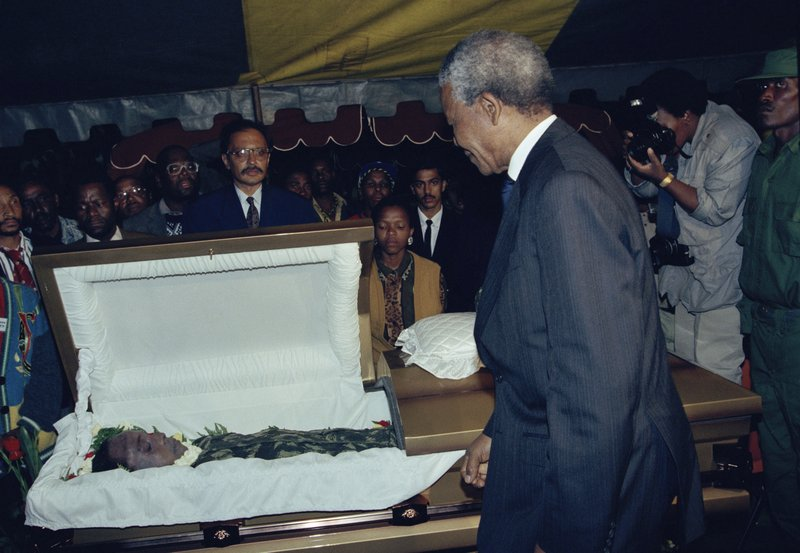 FILE - In this Sunday, April 18, 1993 file photo, African National Congress President Nelson Mandela, right, views the body of slain activist Chris Hani as the body lies in state in a Soweto soccer stadium a day before his burial. (AP Photo/John Parkin, File)