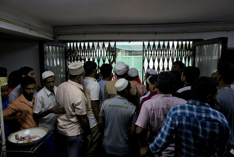 Muslim men leave a mosque after Friday prayers in Colombo, Sri Lanka, Friday, April 26, 2019. Religious leaders cancelled large public gatherings amid warnings of more attacks, along with retaliatory sectarian violence in Sri Lanka though some still held communal Friday prayers at mosques. (AP Photo/Gemunu Amarasinghe)