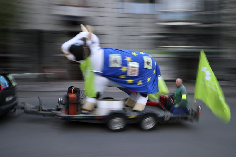 An inflated cow shaped balloon with an EU flag is pulled during a protest by European trade unions in Brussels, Friday, April 26, 2019. (AP Photo/Francisco Seco)