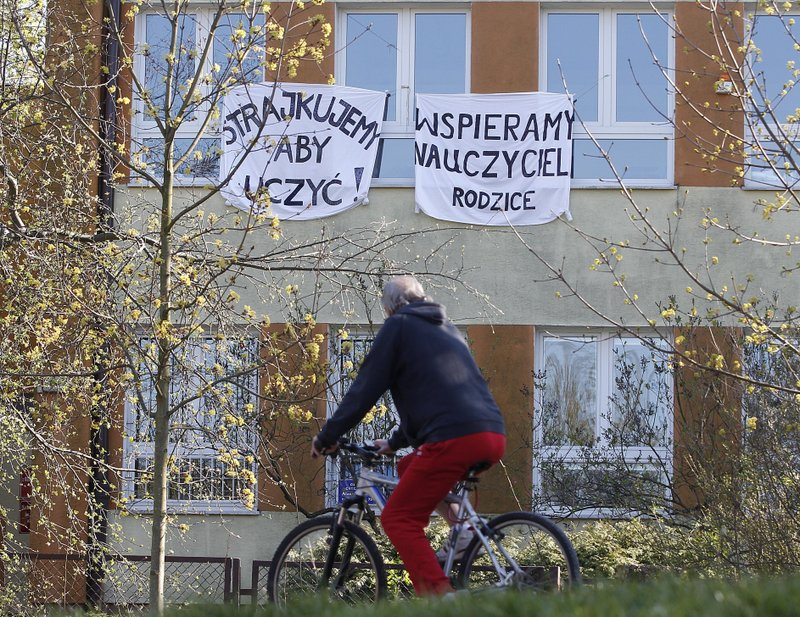 A cyclist rides by a school where teachers are taking part in nationwide pay strike, with banners declaring the participation in the strike and also parent's support for it, in Warsaw, Poland, on Monday, April 15, 2019. (AP Photo/Czarek Sokolowski)