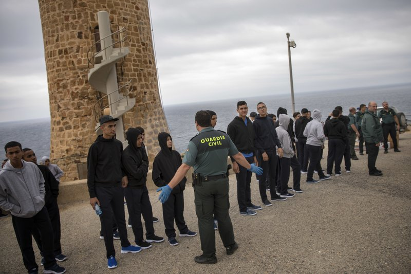 FILE - In this June. 28, 2018 file photo, a Guardia Civil officer stands next to Moroccan migrants after they arrived on the beach sailing on a rubber dinghy near Tarifa, in the south of Spain. (AP Photo/Emilio Morenatti, File)