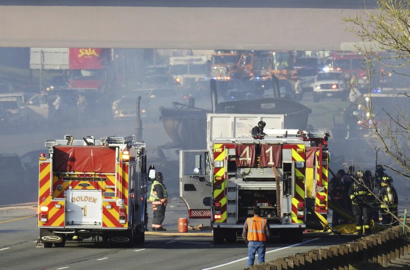 In this Thursday, April 25, 2019 photo, emergency crews work at the scene of a deadly collision on Interstate 70 near the Colorado Mills Parkway in Lakewood, Colo. (Hyoung Chang/The Denver Post via AP)