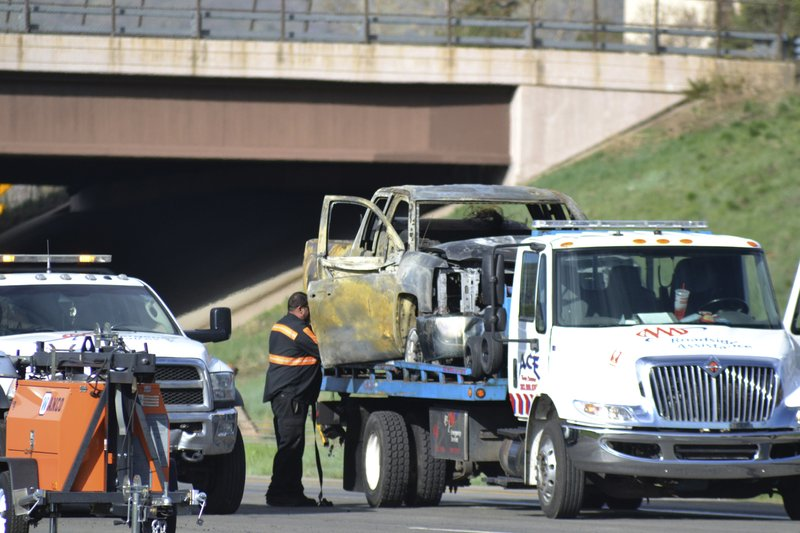 A tow truck driver removes a burned out car at the scene of a fiery crash on I-70 near Colorado Mills Parkway that shut down the highway in both directions on Friday, April 26, 2019. (AP Photo/Peter Banda)
