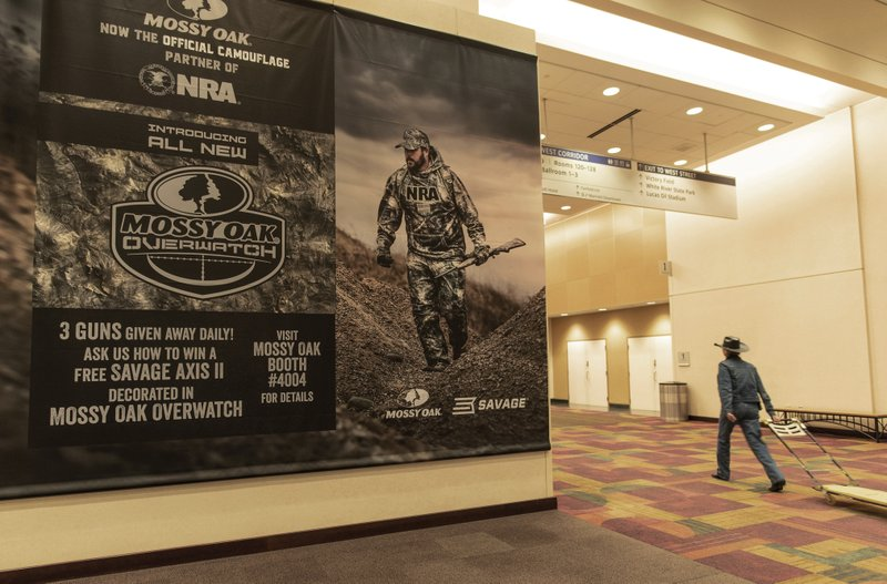 A poster hangs on the wall of the Indianapolis Convention Center on Thursday, April 25, 2019, where members of the National Rifle Association will be holding its 148th annual meetings in Indianapolis. (AP Photo/Lisa Marie Pane)