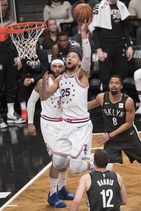 Philadelphia 76ers guard Ben Simmons (25) goes to the basket past Brooklyn Nets guard Spencer Dinwiddie (8) and forward Joe Harris (12) during the second half of Game 4 of a first-round NBA basketball playoff series, Saturday, April 20, 2019, in New York. (AP Photo/Mary Altaffer)