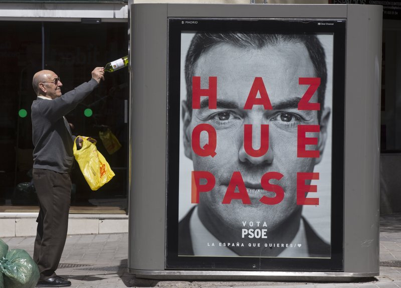 In this Tuesday, April 16, 2019 photo a man deposits an empty wine bottle into a recycling container with an election poster showing the face of Socialist prime minister Pedro Sanchez in Madrid, Spain. (AP Photo/Paul White)