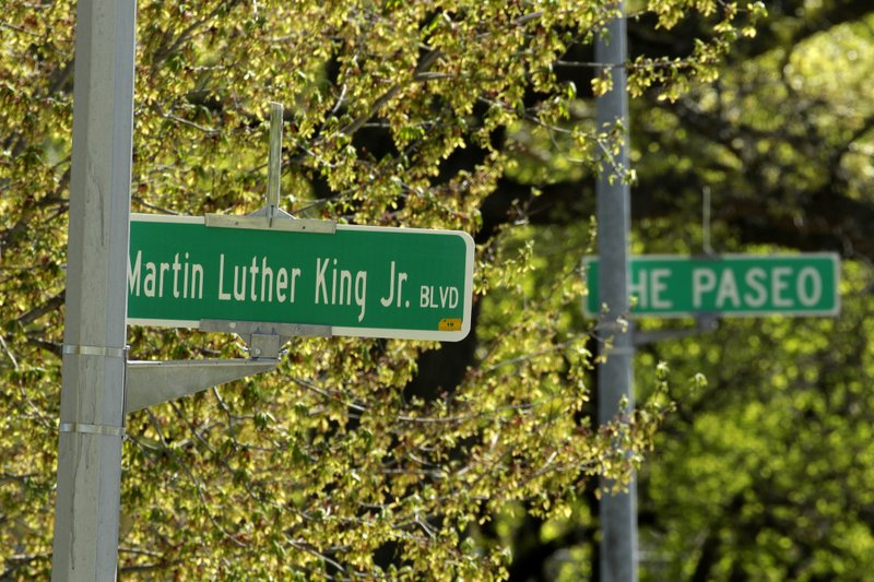 In this photo taken April, 20, 2019, a newly changed sign for Dr. Martin Luther King, Jr. Boulevard stands in contrast to a yet-to-be changed sign for The Paseo in Kansas City, Mo. (AP Photo/Charlie Riedel)