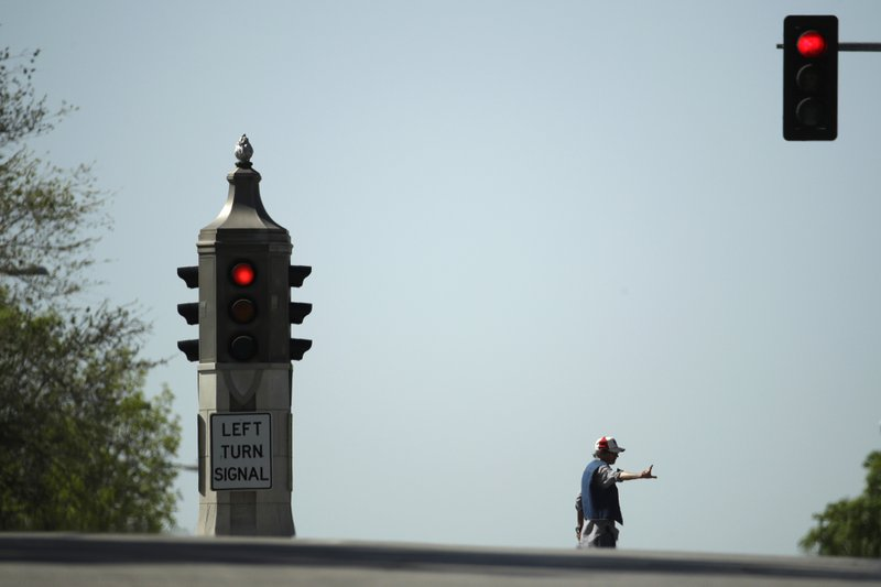 A pedestrian crosses newly-named Dr. Martin Luther King Jr. Boulevard Friday, April 26, 2019, in Kansas City, Mo. (AP Photo/Charlie Riedel)