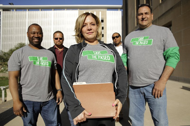 Tara Green, center, holds a petition with 2,857 signatures as she stands with other citizens opposed to changing the name of the Paseo Boulevard to Rev. (AP Photo/Charlie Riedel)