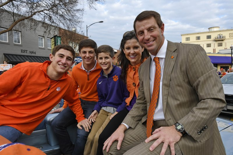 FILE - In this Jan. 14, 2017, file photo, Clemson head coach Dabo Swinney, right, with his wife Kathleen, and sons, Clay, Drew, and Will ride in a vintage car during a parade honoring the NCAA college football champions, in Clemson, S. (AP Photo/Richard Shiro, File)