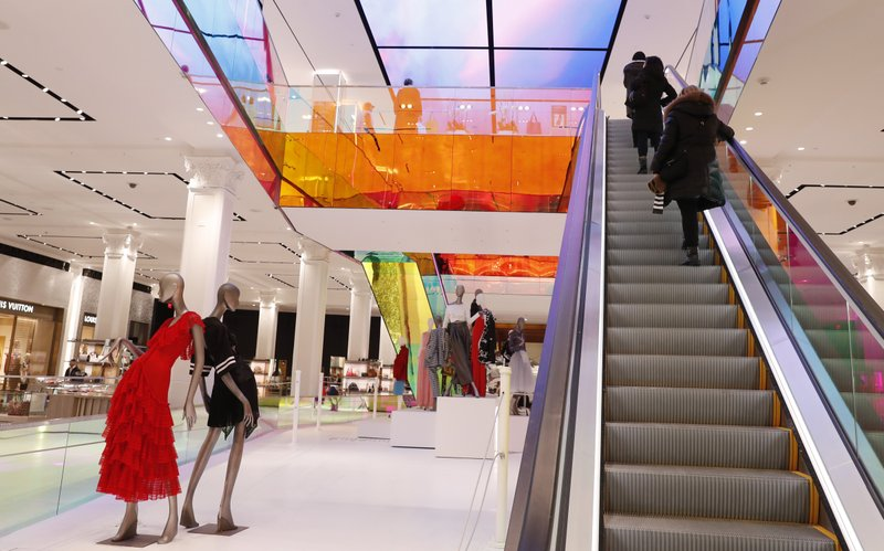 FILE- In this Feb. 20, 2019, file photo shoppers ride the escalator at Saks Fifth Avenue's flagship midtown Manhattan store in New York. (AP Photo/Kathy Willens, File)