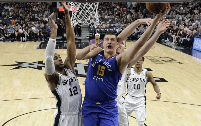 Denver Nuggets center Nikola Jokic (15) shoots around San Antonio Spurs center LaMarcus Aldridge (12) during the first half of Game 6 of an NBA basketball playoff series, Thursday, April 25, 2019, in San Antonio. (AP Photo/Eric Gay)
