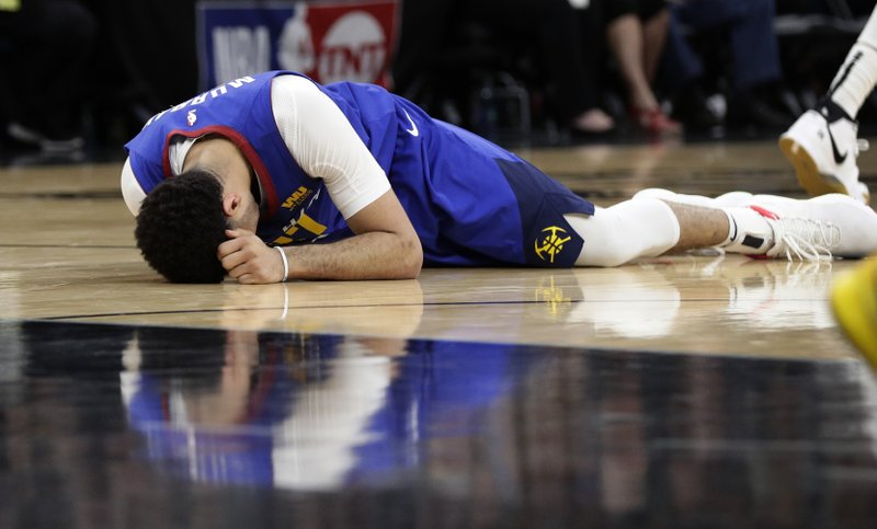 Denver Nuggets guard Jamal Murray (27) lies on the court after after taking a knee to the left thigh during the second half of Game 6 of an NBA basketball playoff series against the San Antonio Spurs, Thursday, April 25, 2019, in San Antonio. (AP Photo/Eric Gay)