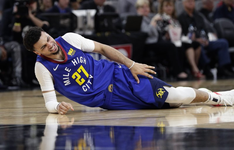 Denver Nuggets guard Jamal Murray (27) reaches for his leg after he was injured during the second half of Game 6 of an NBA basketball playoff series against the San Antonio Spurs, Thursday, April 25, 2019, in San Antonio. (AP Photo/Eric Gay)