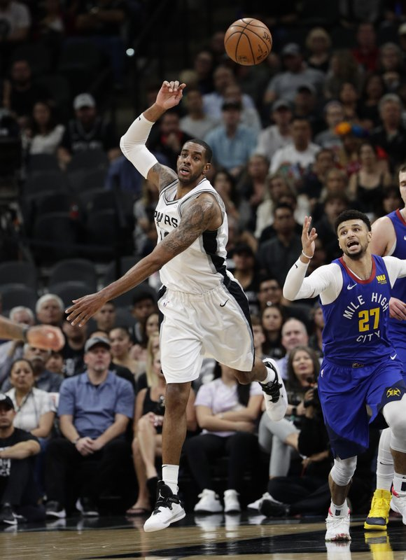 San Antonio Spurs center LaMarcus Aldridge (12) and Denver Nuggets guard Jamal Murray (27) chase a rebound during the first half of Game 6 of an NBA basketball playoff series, Thursday, April 25, 2019, in San Antonio. (AP Photo/Eric Gay)