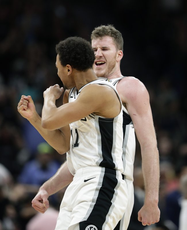 San Antonio Spurs guard Bryn Forbes (11) and San Antonio Spurs center Jakob Poeltl, right, celebrate a score against the Denver Nuggets during the second half of Game 6 of an NBA basketball playoff series, Thursday, April 25, 2019, in San Antonio. (AP Photo/Eric Gay)