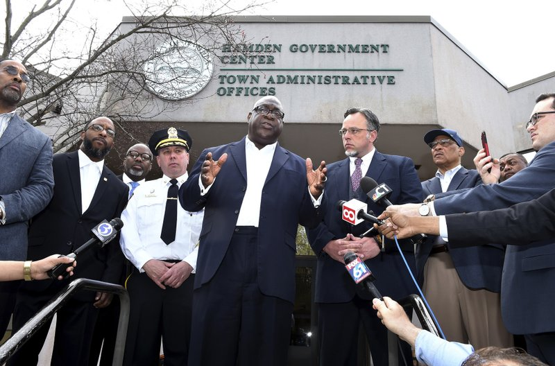 Rev Boise Kimber, center, flanked by Hamden Acting Police Chief John Cappiello, left, and Hamden Mayor Curt Leng, right, addresses the media outside of the Hamden Government Center after a meeting between the town officials and local clergy concerning the recent shooting by a Hamden police officer, Friday, April 19, 2019 in Hamden, Conn.. (Arnold Gold/Hearst Connecticut Media via AP)