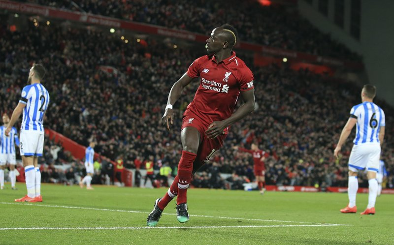 Liverpool's Sadio Mane, centre, celebrates after scoring his side's fourth goal during the English Premier League soccer match between Liverpool and Huddersfield Town at Anfield Stadium, in Liverpool, England, Friday, April 26, 2019.(AP Photo/Jon Super)