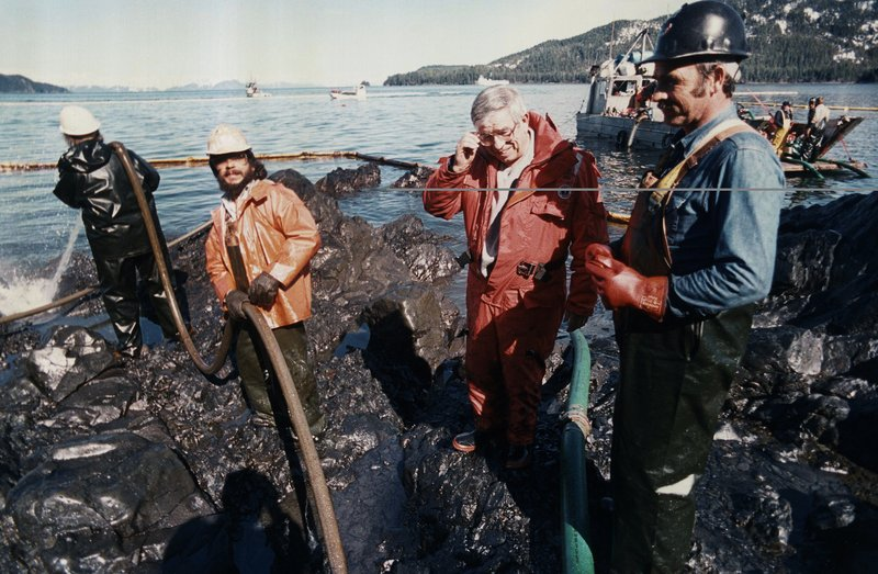 FILE - In this April 21, 1969, file photo, Secretary of the Interior Manuel Lujan, third from left, looks at the oil clean up on a beach on Naked Island, in the Prince William Sound in Alaska. (AP Photo/Stapleton, File)