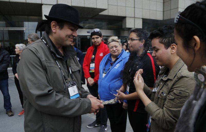 David Jackson, right, takes in the smoke from the burning sage held by First Nation Chief Duke Peltier during a cleansing ceremony outside the First Championship robotics competition, Friday, April 26, 2019, in Detroit. (AP Photo/Carlos Osorio)