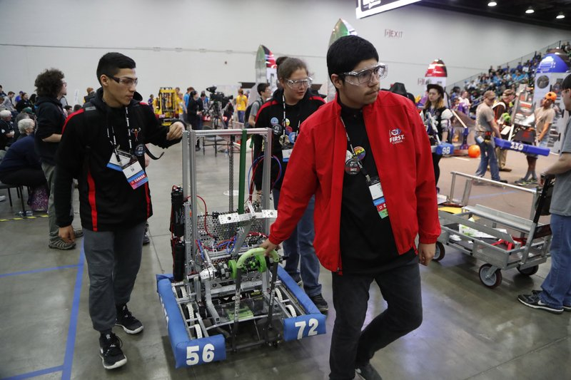 From left, DJ Maiangowi, Jason Mishibijima and Sterling Pangowish push their robot from the arena to the pits during the First Championship robotics competition, Friday, April 26, 2019, in Detroit. (AP Photo/Carlos Osorio)