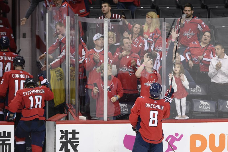 Washington Capitals left wing Alex Ovechkin (8), of Russia, gives away his stick as the team leaves the ice after Game 7 of an NHL hockey first-round playoff series against the Carolina Hurricanes, Wednesday, April 24, 2019, in Washington. (AP Photo/Nick Wass)