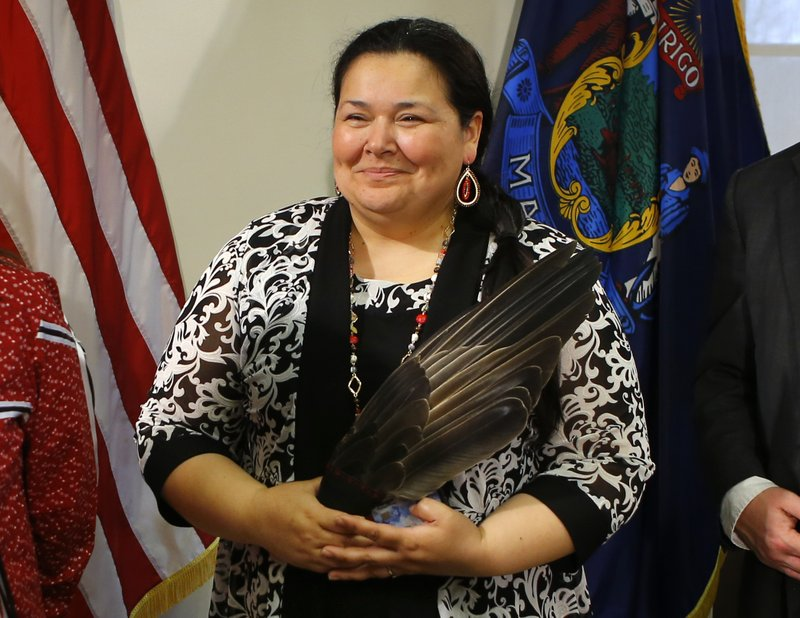 Clarissa Sabattus, Tribal Chief of the Houlton Band of Maliseet Indians, holds eagle feathers during the signing ceremony to establish Indigenous Peoples' Day, Friday, April 26, 2019, at the State House in Augusta, Maine. (AP Photo/Robert F. Bukaty)