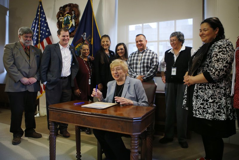 Maine Gov. Janet Mills signs a bill to establish Indigenous Peoples' Day, Friday, April 26, 2019, at the State House in Augusta, Maine. (AP Photo/Robert F. Bukaty)