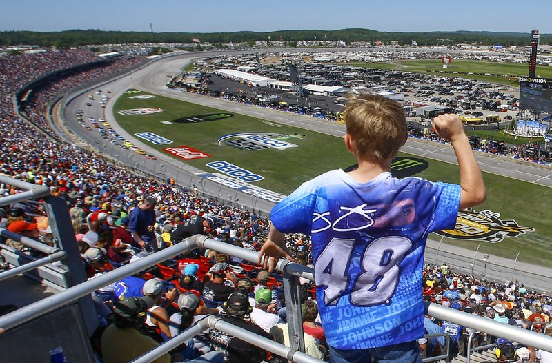 FILE - In this April 29, 2018, file photo, a young fan cheers as racers go by during a NASCAR Talladega auto race at Talladega Superspeedway, in Talladega, Ala. (AP Photo/Butch Dill, File)