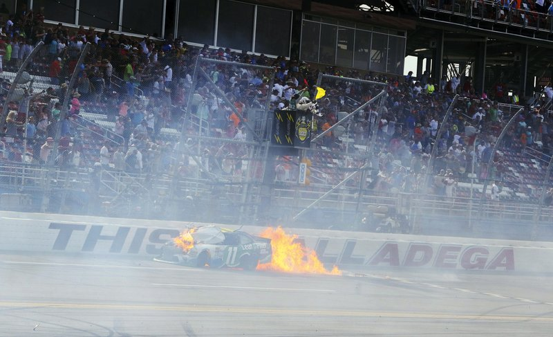 FILE - In this April 30, 2016, file photo, flames come from Blake Koch's car after a wreck just before the finish of the NASCAR Xfinity Series auto race at Talladega Superspeedway, in Talladega, Ala. (AP Photo/Jay Alley, File)