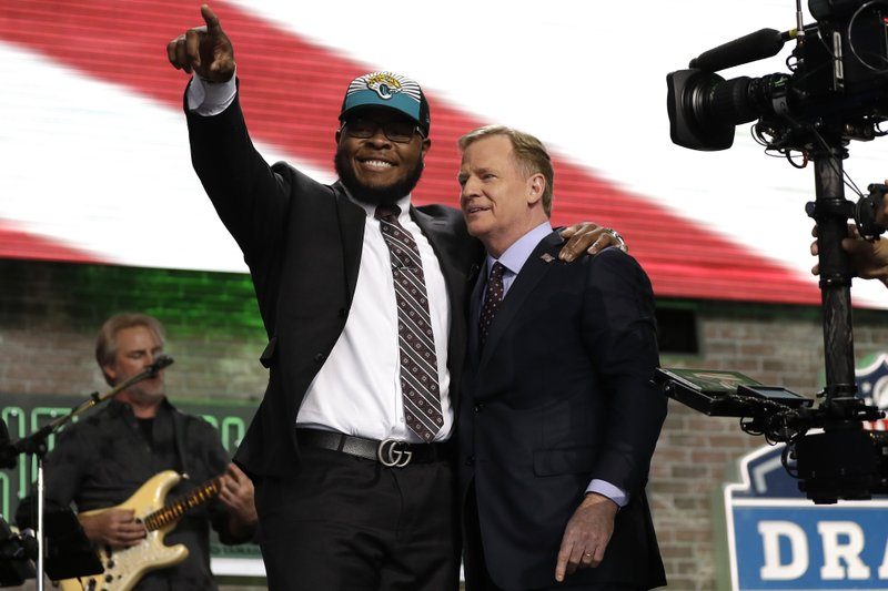 Florida's Jawaan Taylor poses with NFL Commissioner Roger Goodell after the Jacksonville Jaguars selected Taylor in the second round of the NFL football draft, Friday, April 26, 2019, in Nashville, Tenn. (AP Photo/Mark Humphrey)