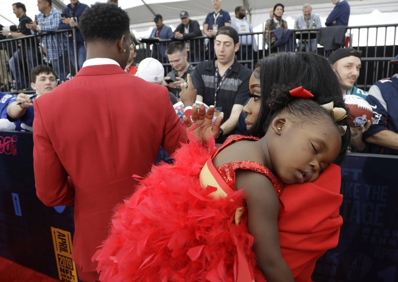 Louisiana State cornerback Greedy Williams signs autographs as his daughter Cloie Williams is held by her mother Taquana Houston on the red carpet ahead of the first round at the NFL football draft, Thursday, April 25, 2019, in Nashville, Tenn. (AP Photo/Steve Helber)