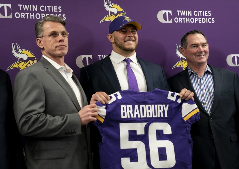 Minnesota Vikings first-round draft pick Garrett Bradbury, center, holds his jersey next to general manager Rick Spielman, left, and head coach Mike Zimmer during an NFL football news conference in Eagan, Minn. (Renee Jones Schneider/Star Tribune via AP)