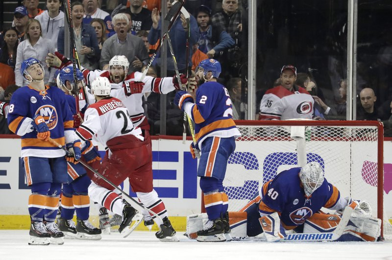 Carolina Hurricanes center Jordan Staal, center left, reacts after scoring an overtime goal on New York Islanders goaltender Robin Lehner (40), of Sweden, during Game 1 of an NHL hockey second-round playoff series, Friday, April 26, 2019, in New York. (AP Photo/Julio Cortez)