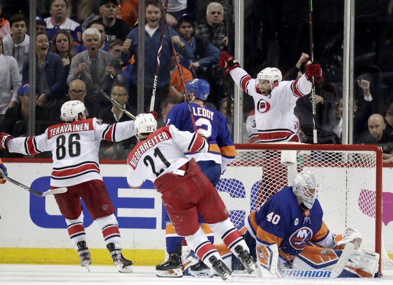 Carolina Hurricanes center Jordan Staal, top right, reacts after scoring an overtime goal on New York Islanders goaltender Robin Lehner (40), of Sweden, during Game 1 of an NHL hockey second-round playoff series, Friday, April 26, 2019, in New York. (AP Photo/Julio Cortez)