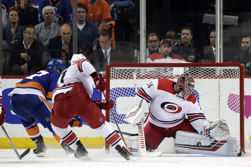 Carolina Hurricanes goaltender Petr Mrazek, right, of the Czech Republic, blocks a shot form New York Islanders left wing Anders Lee, left, during the third period of Game 1 of an NHL hockey second-round playoff series, Friday, April 26, 2019, in New York. (AP Photo/Julio Cortez)