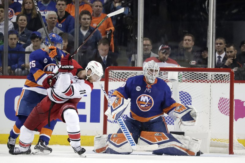 New York Islanders goaltender Robin Lehner, of Sweden, eyes the puck as teammate defenseman Devon Toews (25) blocks Carolina Hurricanes center Jordan Staal (11) during the second period of Game 1 of an NHL hockey second-round playoff series, Friday, April 26, 2019, in New York. (AP Photo/Julio Cortez)