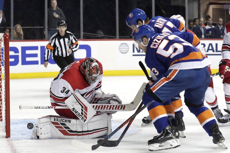 The puck bounces off Carolina Hurricanes goaltender Petr Mrazek (34), of the Czech Republic, as New York Islanders center Casey Cizikas (53) and left wing Matt Martin (17) attack during the second period of Game 1 of an NHL hockey second-round playoff series, Friday, April 26, 2019, in New York. (AP Photo/Julio Cortez)