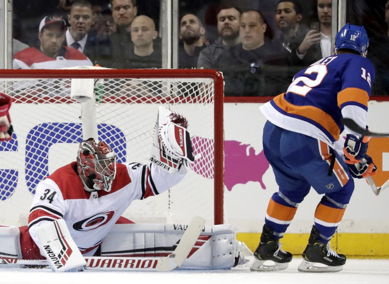 Carolina Hurricanes goaltender Petr Mrazek (34), of the Czech Republic, makes a glove save against New York Islanders right wing Josh Bailey (12) during the first period of Game 1 of an NHL hockey second-round playoff series, Friday, April 26, 2019, in New York. (AP Photo/Julio Cortez)