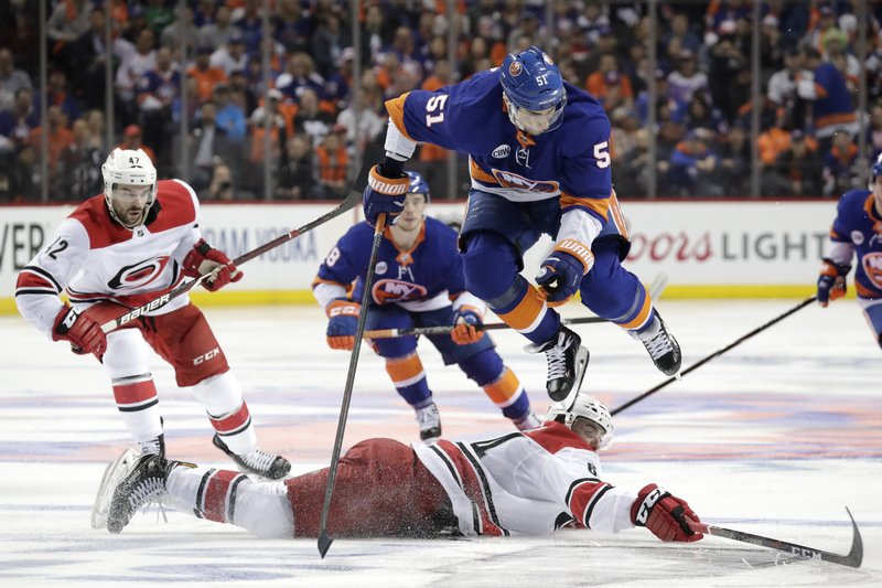 New York Islanders center Valtteri Filppula (51), of Finland, leaps over Carolina Hurricanes center Clark Bishop, bottom, while competing for the puck during the second period of Game 1 of an NHL hockey second-round playoff series, Friday, April 26, 2019, in New York. (AP Photo/Julio Cortez)