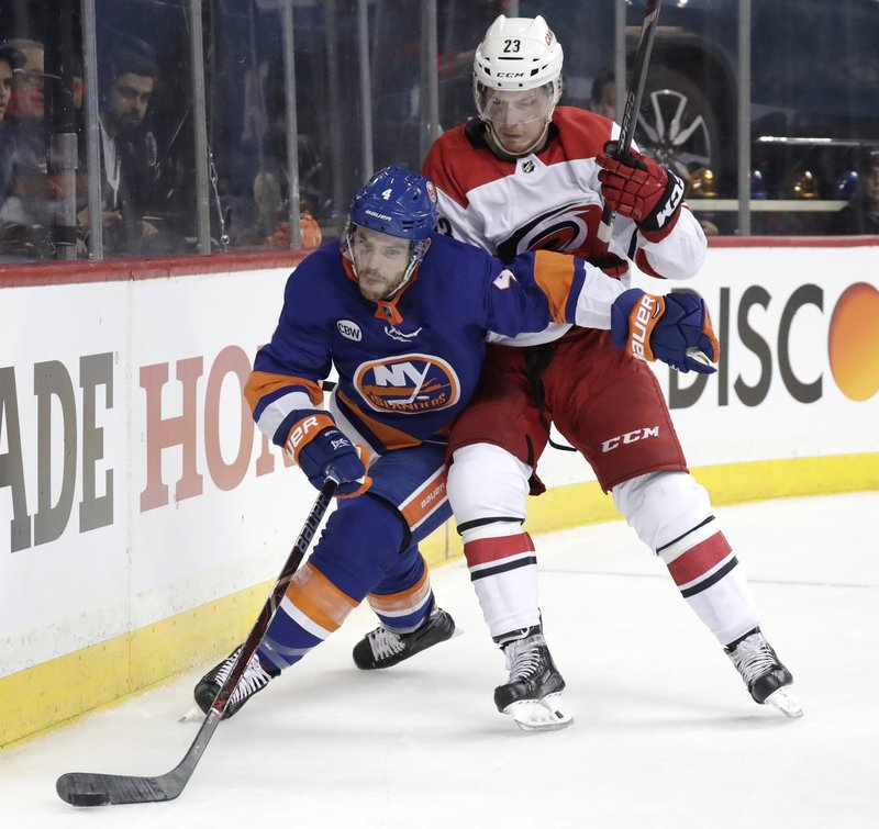 New York Islanders defenseman Thomas Hickey (4) tries to control the puck as Carolina Hurricanes left wing Brock McGinn (23) challenges him during the first period of Game 1 of an NHL hockey second-round playoff series, Friday, April 26, 2019, in New York. (AP Photo/Julio Cortez)