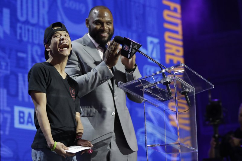 Baltimore Ravens fan Miles Davis, left, announces the Ravens selection of Louisiana Tech's Jaylon Ferguson during the third round of the NFL football draft, Friday, April 26, 2019, in Nashville, Tenn. (AP Photo/Mark Humphrey)
