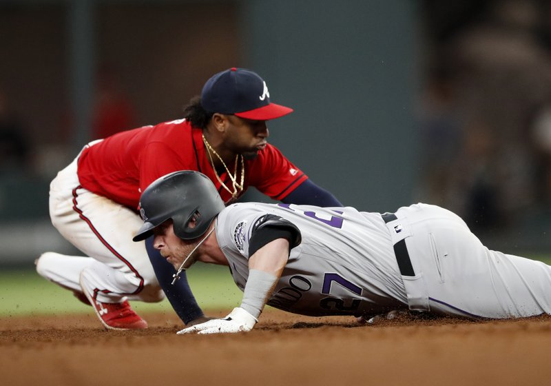 Colorado Rockies' Trevor Story (27) is safe at second base with a double as Atlanta Braves second baseman Ozzie Albies, top, applies a late tag in the sixth inning of a baseball game Friday, April 26, 2019, in Atlanta. (AP Photo/John Bazemore)