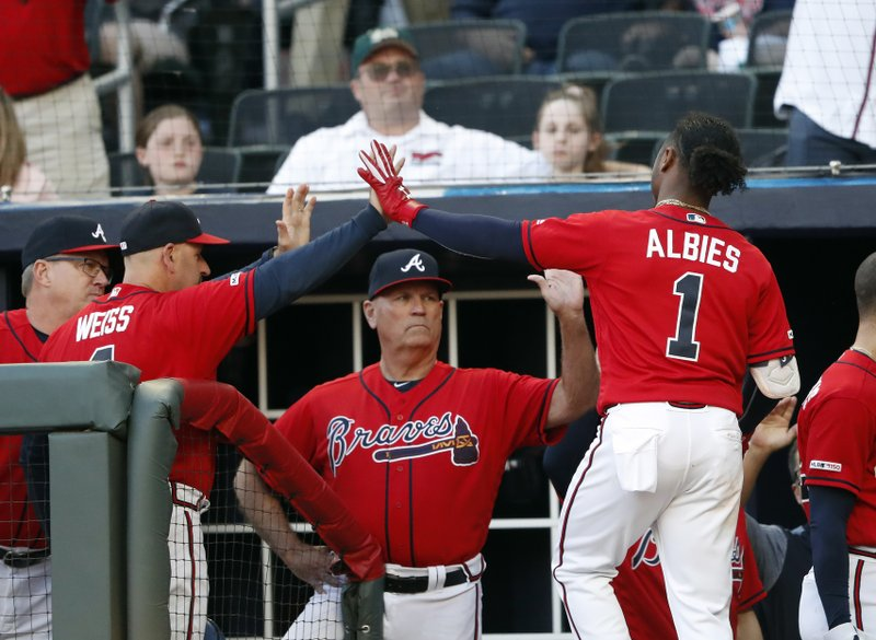 Atlanta Braves second baseman Ozzie Albies (1) is greeted at the dugout by bench coach Walt Weiss (4), left, and manager Brian Snitker (43) after scoring on a Josh Donaldson double in the first inning of a baseball game against the Colorado Rockies, Friday, April 26, 2019, in Atlanta.(AP Photo/John Bazemore)