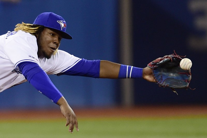 Toronto Blue Jays third baseman Vladimir Guerrero Jr. (27) dives for single by Oakland Athletics' Ramon Laureano during eighth-inning baseball game action in Toronto, Friday, April 26, 2019. (Frank Gunn/The Canadian Press via AP)