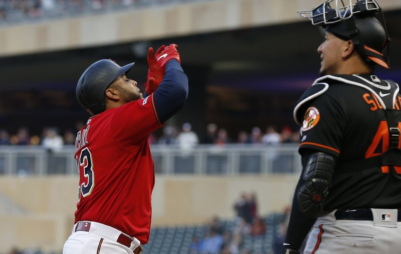 Minnesota Twins' Nelson Cruz, left, celebrates his solo home run off Baltimore Orioles' pitcher Alex Cobb as he passes Orioles catcher Jesus Sucre in the first inning of a baseball game Friday, April 26, 2019, in Minneapolis. (AP Photo/Jim Mone)