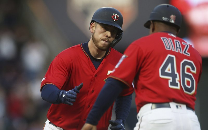 Minnesota Twins' C.J. Cron, left, rounds the bases on a solo home run off Baltimore Orioles' pitcher Alex Cobb in the first inning of a baseball game Friday, April 26, 2019, in Minneapolis. (AP Photo/Jim Mone)